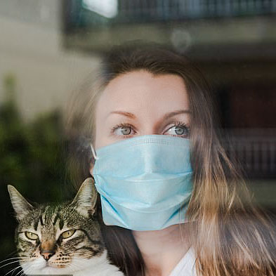Cat with owner wearing a mask during coronavirus lockdown