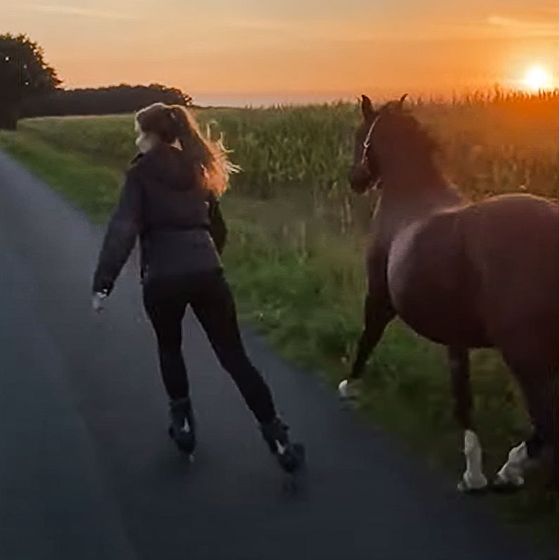Woman rollerblades with her horse